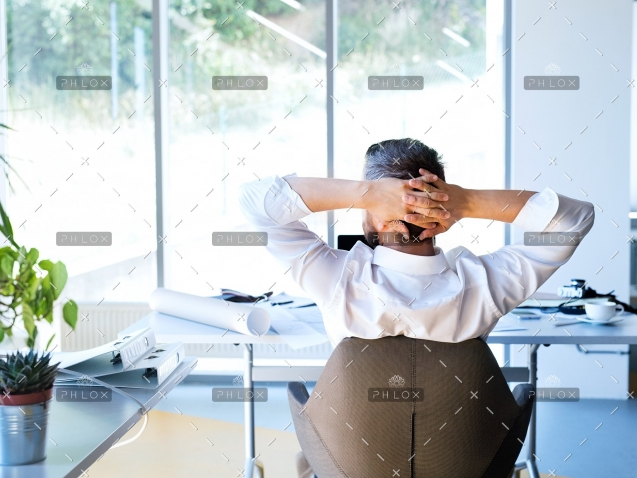 Businessman-at-the-desk-in-his-office-resting.-2